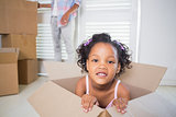 Cute daughter sitting in moving box