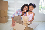 Cute daughter unpacking her teddy bear with mother