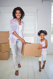 Cute daughter unpacking moving boxes with her mother