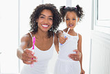 Pretty mother and daughter showing toothbrushes