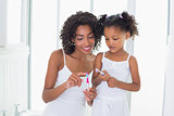 Pretty mother showing her daughter her toothbrush