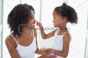 Cute daughter putting face cream on mothers nose