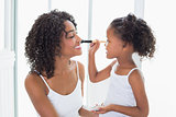 Cute daughter putting makeup on her mothers face