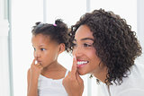 Pretty mother putting face cream on with her daughter