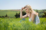 Pretty blonde thinking while sitting on grass