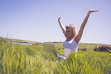 Pretty blonde sitting on grass using her laptop and cheering
