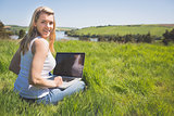 Pretty blonde sitting on grass using her laptop smiling at camera