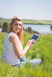 Pretty blonde sitting on grass using her tablet smiling at camera