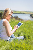 Pretty blonde sitting on grass using her tablet