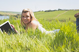 Pretty blonde lying on grass using her tablet smiling at camera