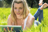Pretty blonde lying on grass using her tablet
