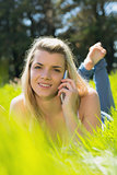 Pretty blonde lying on grass talking on phone smiling at camera