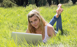 Pretty blonde lying on grass using laptop smiling at camera