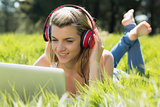 Pretty blonde lying on grass using laptop listening to music
