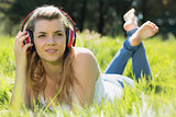 Pretty blonde lying on grass listening to music