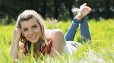 Pretty blonde lying on grass with headphones around neck