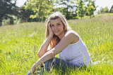 Pretty blonde smiling at camera sitting on grass