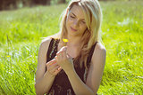 Pretty blonde in sundress sitting on grass holding yellow flower