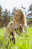 Pretty blonde in sundress sitting on grass holding yellow flower