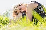 Pretty blonde in sundress sitting on grass