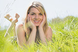 Pretty blonde in sundress lying on grass smiling at camera