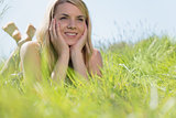 Pretty blonde in sundress lying on grass smiling