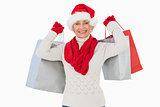 Festive woman smiling at camera holding shopping bags