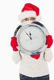 Festive woman looking at camera holding clock