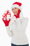 Festive woman listening and holding gift