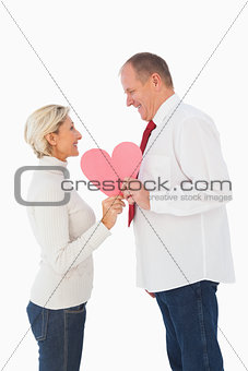 Older affectionate couple holding pink heart shape