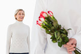 Man hiding bouquet of roses from older woman