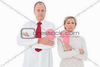 Older couple standing holding broken pink heart