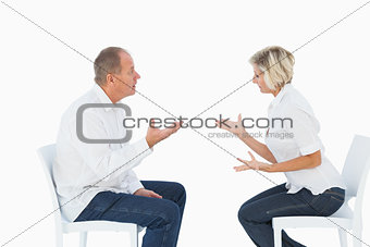 Older couple sitting in chairs arguing