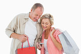 Smiling older couple holding shopping bags looking at smartphone