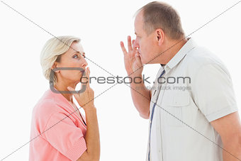 Older couple holding hands to mouth for silence