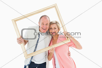 Older couple smiling at camera through picture frame