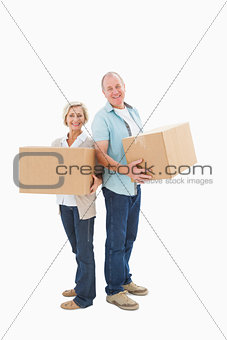 Older couple smiling at camera holding moving boxes