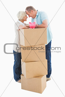 Older couple smiling at each other with moving boxes and piggy bank