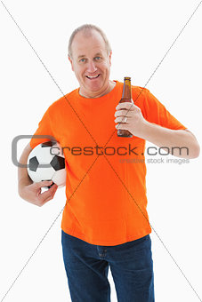 Mature man in orange tshirt holding football and beer
