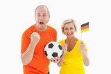 Happy german couple cheering at camera holding ball