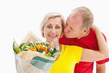 Mature man kissing his partner holding flowers