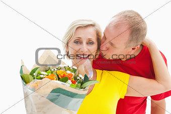 Mature man kissing his partner holding flowers