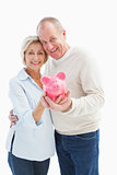 Happy mature couple smiling at camera showing piggy bank