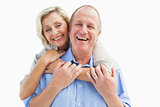 Happy mature couple embracing smiling at camera