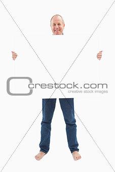 Mature man smiling at camera and holding card