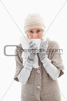 Mature woman in winter clothes holding mug