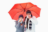 Mature couple blowing their noses under umbrella