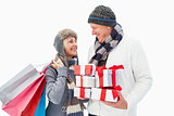 Mature couple in winter clothes holding gifts