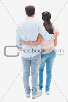 Attractive young couple standing with arms around
