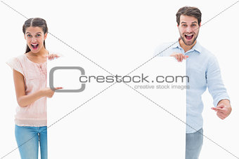 Attractive young couple smiling at camera holding poster